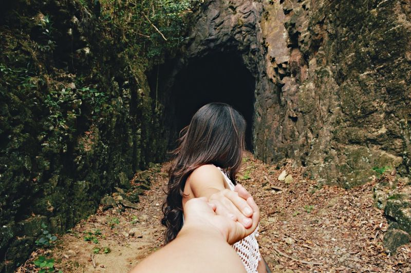 Cropped Image Of Man Holding Woman Hand Against Rock In Forest