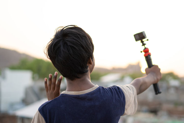 Rear view of boy photographing