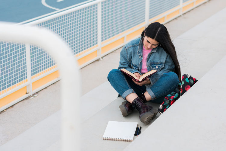 Young woman using mobile phone while sitting on book