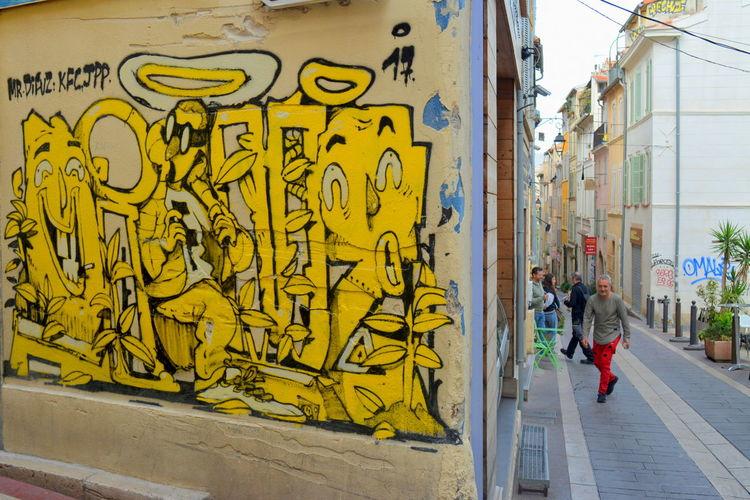Rear view of man walking on graffiti wall