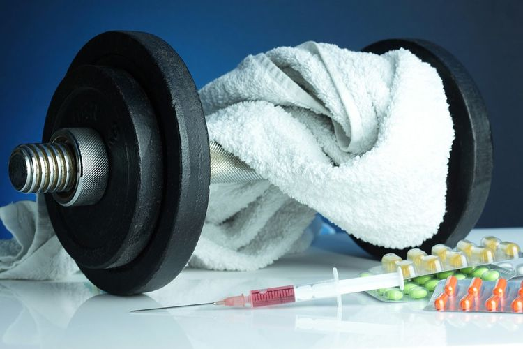 Close-up of pills and syringe by dumbbells on table