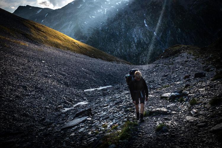 Full length of hiker walking on rocks