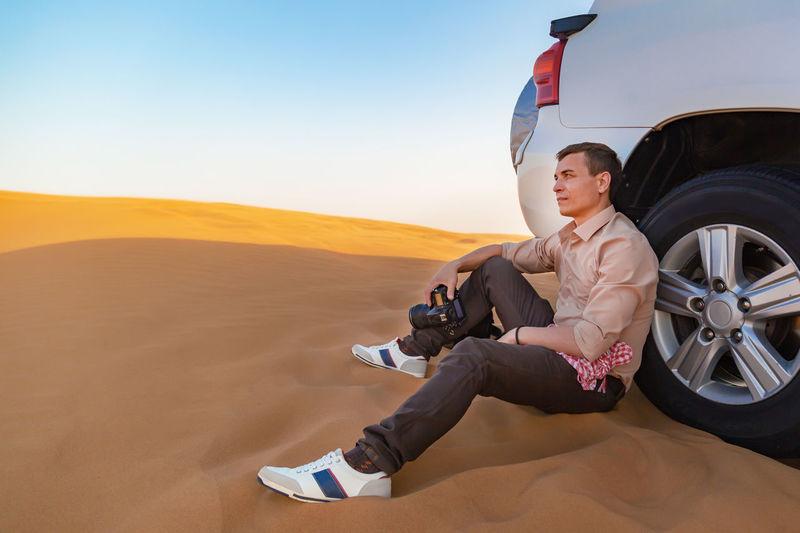 Man sitting on desert against sky