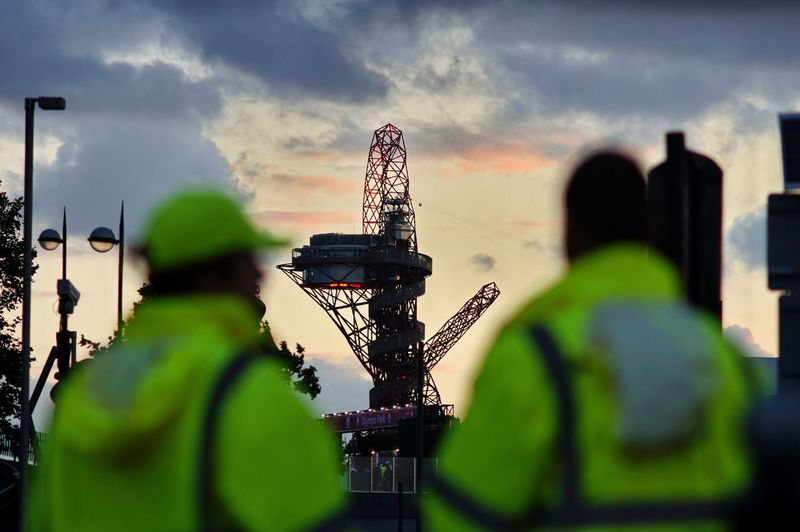 Rear view of workers looking at rig