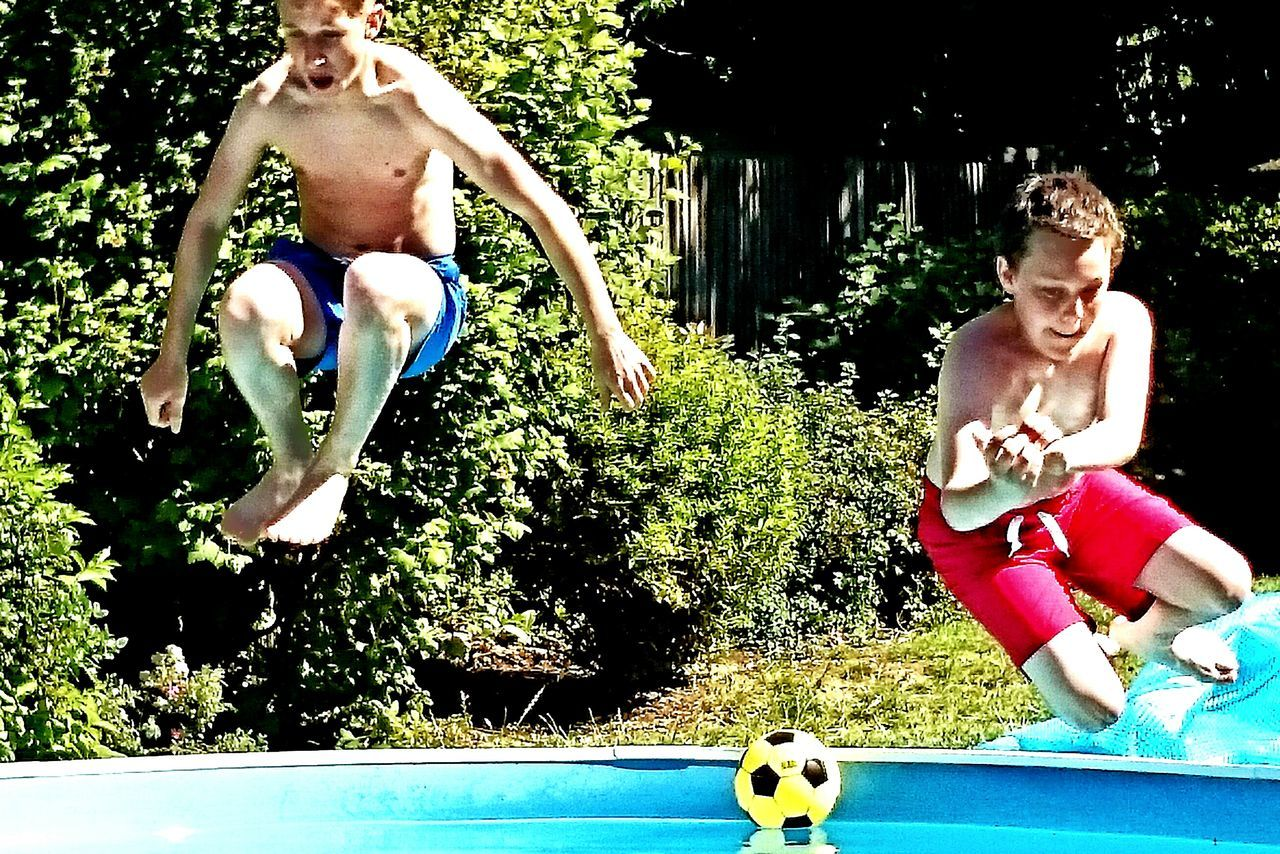 two people, real people, leisure activity, day, togetherness, shirtless, front view, tree, outdoors, mid-air, playing, young adult, young men, jumping, skill, young women, sport, full length, swimming pool, friendship