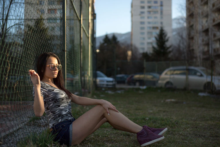 Young woman sitting by chainlink fence on field