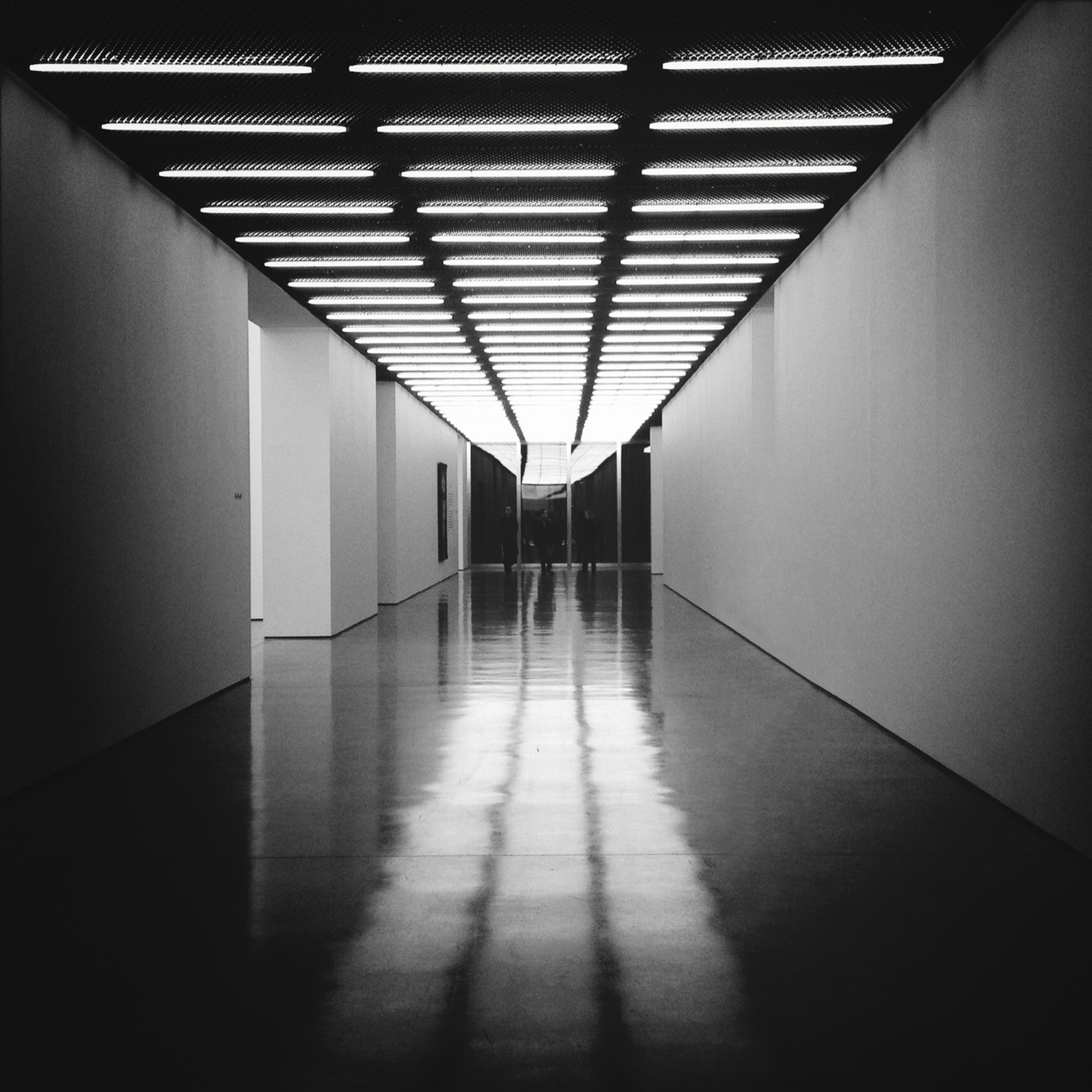 indoors, ceiling, corridor, illuminated, flooring, tiled floor, empty, architecture, built structure, lighting equipment, the way forward, absence, diminishing perspective, wall - building feature, floor, wall, tile, pattern, no people, interior