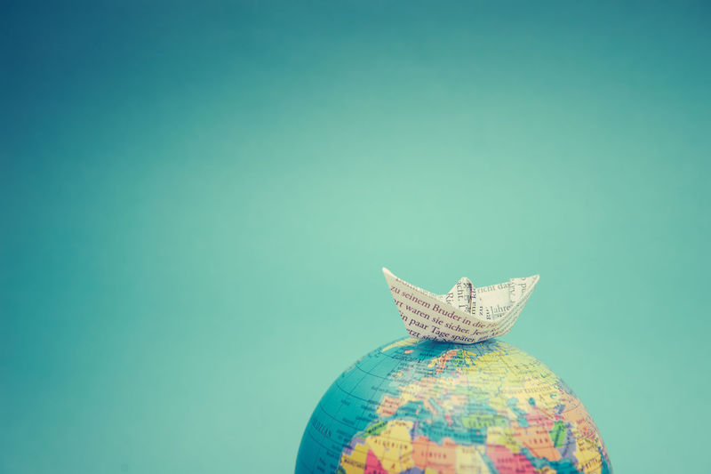 Close up of paper boat on globe over blue background