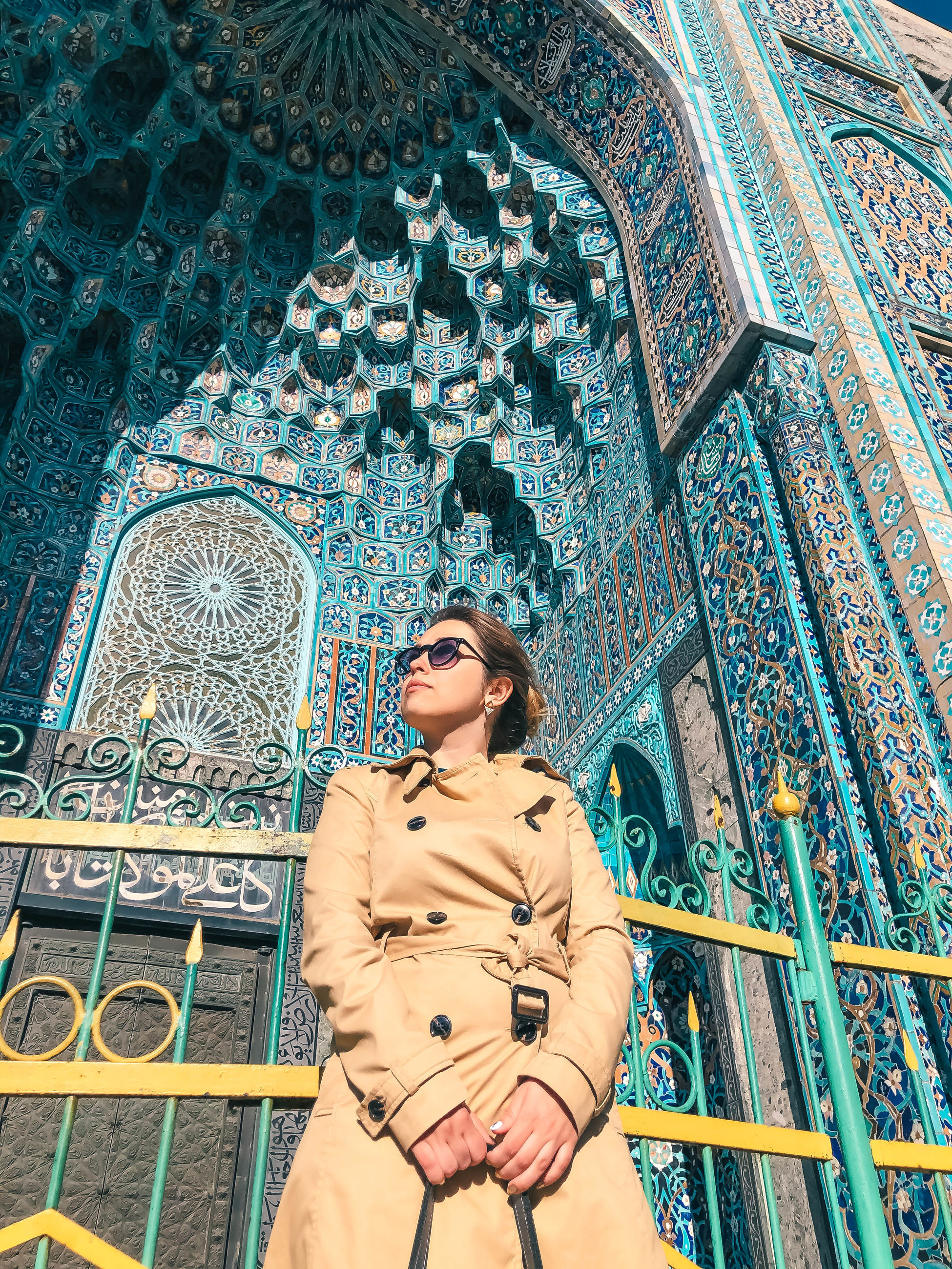 one person, architecture, adult, women, young adult, front view, low angle view, pattern, leisure activity, three quarter length, clothing, built structure, lifestyles, standing, portrait, fashion, religion, spirituality, place of worship, travel destinations, day, casual clothing, looking, building exterior, belief, smiling, outdoors, building, looking up, glasses
