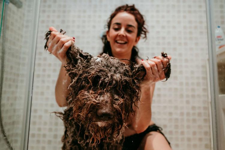 Smiling woman washing dog