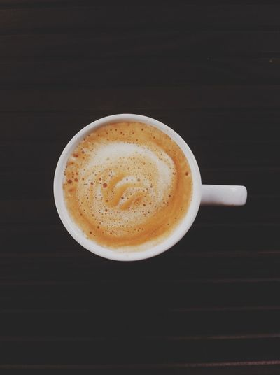 Close-up of cappuccino on table against black background