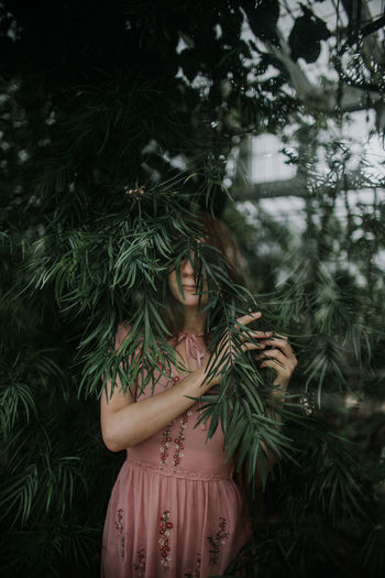 Midsection of woman standing by tree