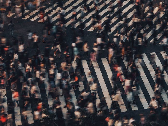 Blur image of people walking on zebra crossing