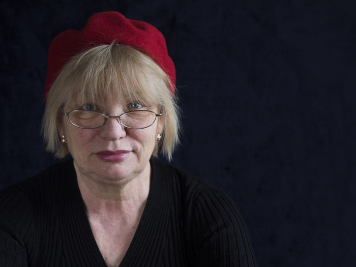 Portrait Of Mature Woman With Red Cap Against Black Background