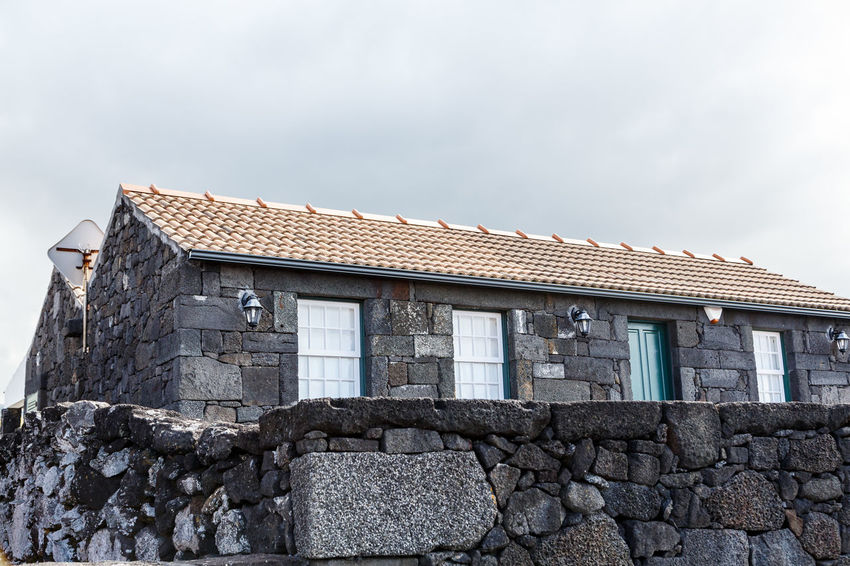Azores Pico Island Traditional House Architecture Basaltic Rock Building Building Exterior Built Structure Cloud - Sky Day House Low Angle View Nature No People Outdoors Residential District Roof Roof Tile Sky Solid Stone Wall Wall Window