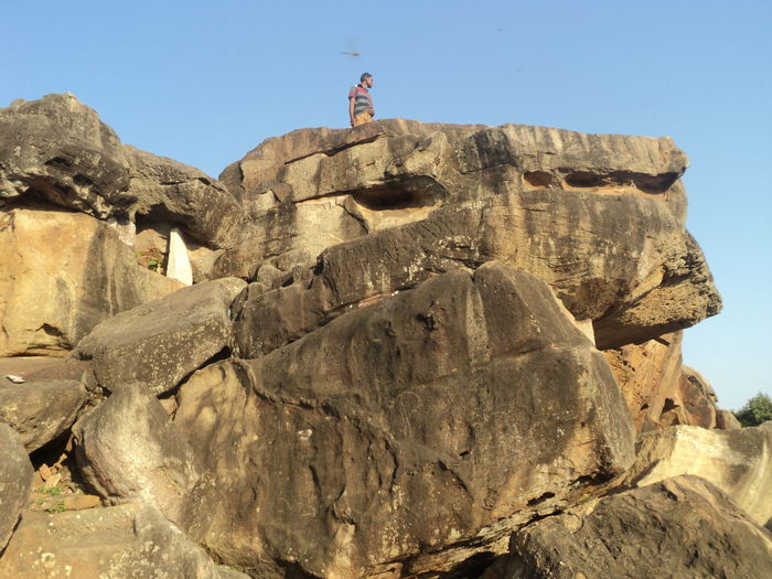 Low angle view of man standing on rock formations against clear sky