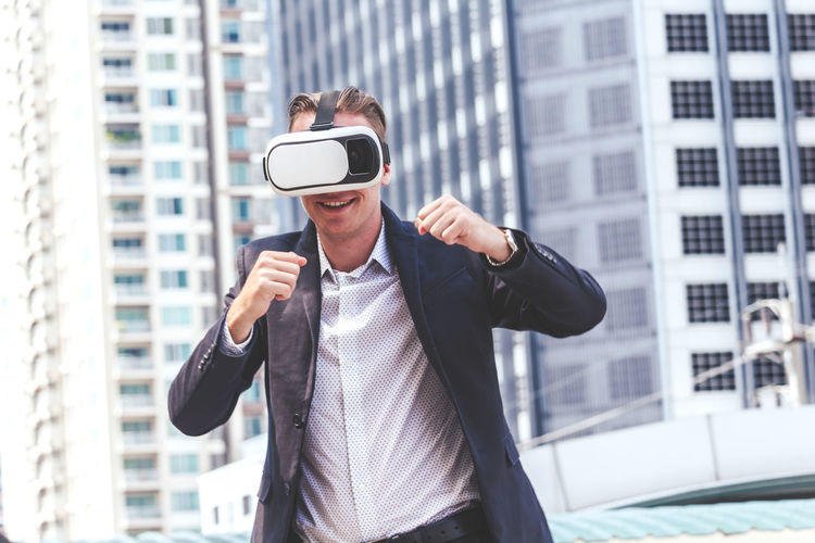 Smiling businessman gesturing while wearing virtual reality in city