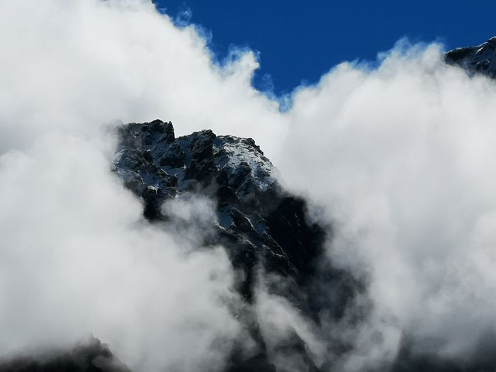 Low angle view of clouds over mountain against sky