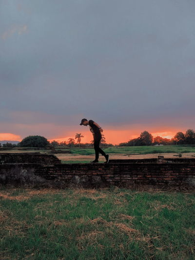 Man walking on brick wall against sky during sunset
