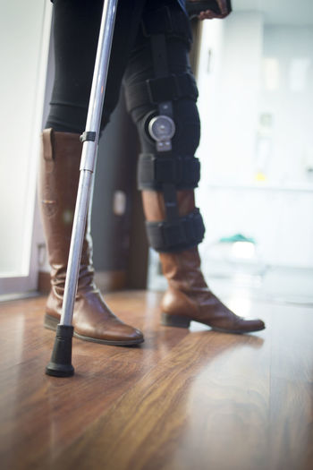 Low section of woman with crutch standing on hardwood floor