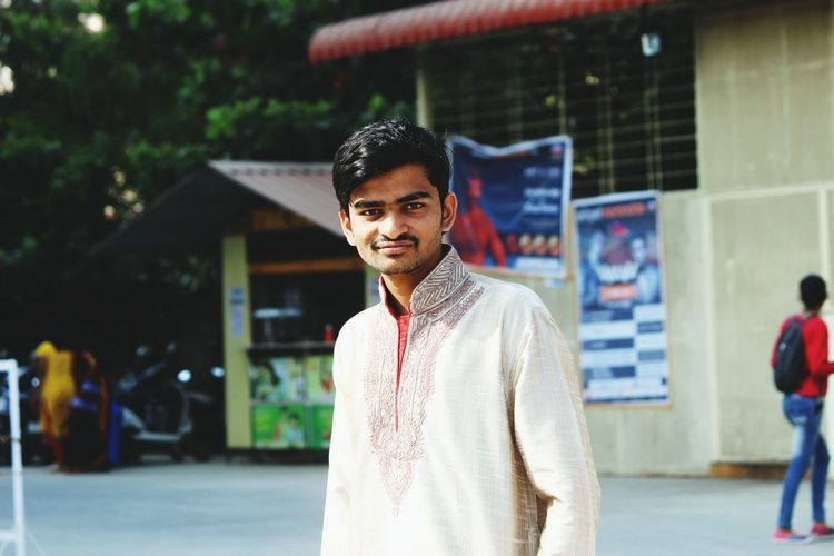 Portrait of young man in kurta standing against built structure
