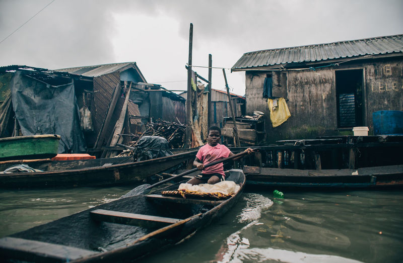 Makoko Slum Architecture Building Building Exterior Built Structure Canal Day Men Mode Of Transportation Nature Nautical Vessel Occupation One Person Outdoors Real People Sky Transportation Water Waterfront