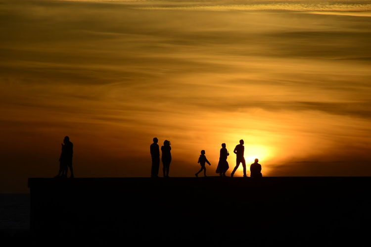 Silhouette people by sea against sky during sunset