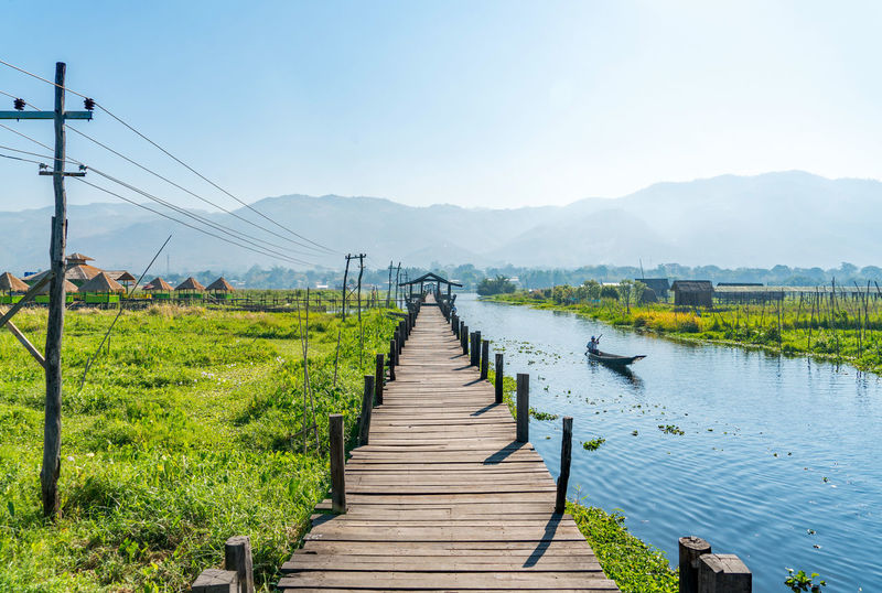 Lake Inle Pier Beauty In Nature Bridge - Man Made Structure Burma Cable Clear Sky Connection Day Electricity Pylon Inle Lake Lake Landscape Mountain Mountain Range Myanmar Nature No People Outdoors Scenics Sky The Way Forward Tranquil Scene Tranquility Tree