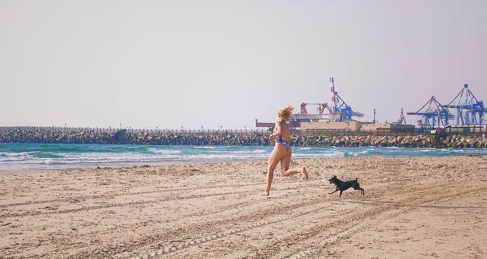 Woman in bikini with dog running on beach against sky