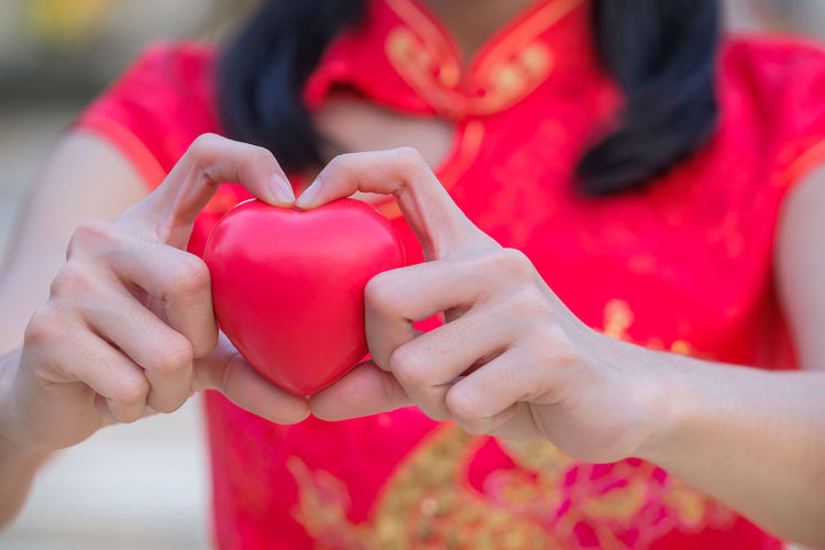 Close-up of woman holding red heart shape