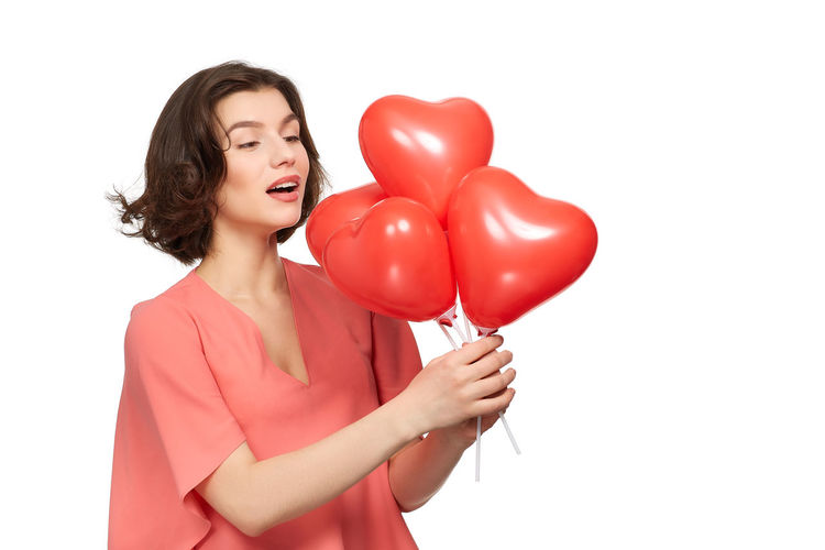 Close-up of a young woman holding heart shape over white background