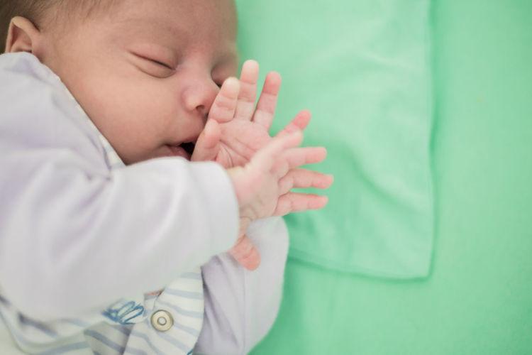 Close-up of cute baby boy sleeping on crib