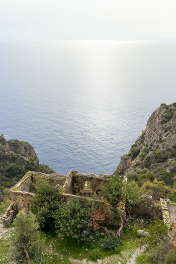 An above view of the roofless ruins of a cliff top house looking down on a calm Mediterranean sea. Architecture Beauty In Nature Day High Angle View Horizon Horizon Over Water Idyllic Land Nature No People Outdoors Rock Rock - Object Scenics - Nature Sea Sky Solid Tranquil Scene Tranquility Water