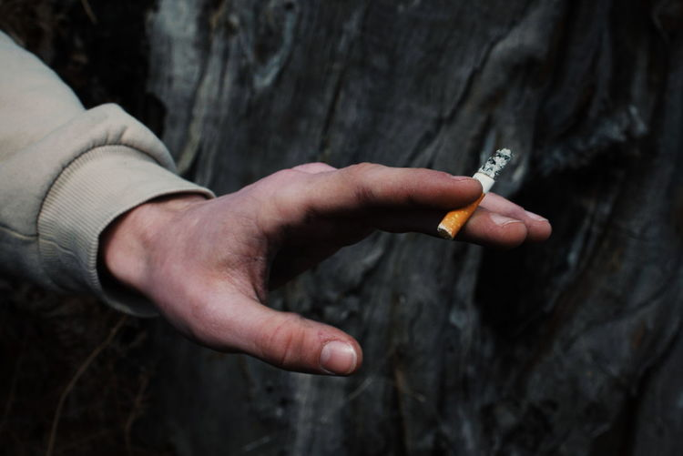 Hand that holds a cigarette in the forest