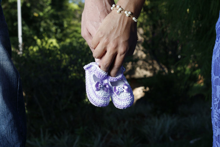 Cropped image of couple holding purple baby booties