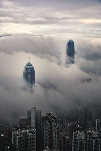 Buildings in city against cloudy sky