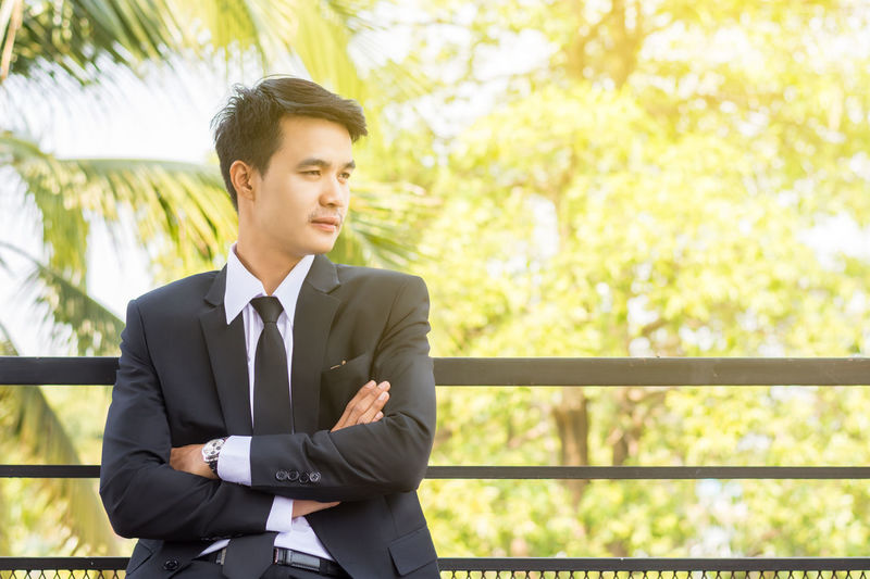Handsome Young Man With Arms Crossed Leaning On Railing Against Trees