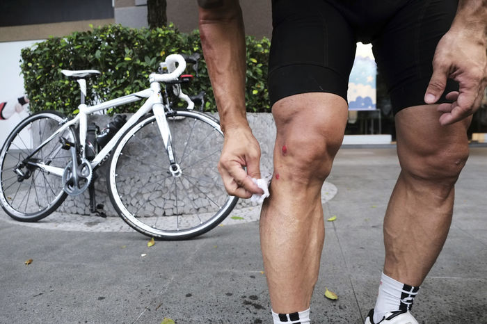 Close-up of cyclist cleaning wounds on injured leg after falling from bike. Adult Athlete Bicycle Bruises Clean Cleaning Cycling Cyclist Day Human Leg Hurt Injured Injury Leg One Man Only One Person Outdoors Pain People Sport Sportsman Wounds