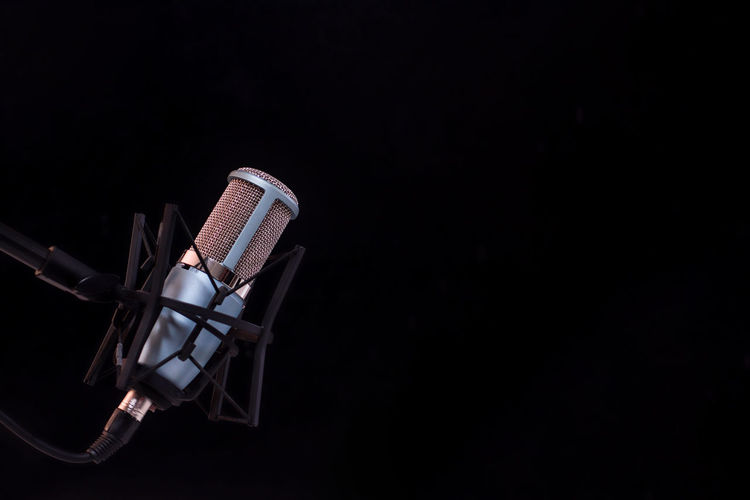 Microphone on black background Black Background Studio Shot Microphone Copy Space Input Device Indoors  Arts Culture And Entertainment Music No People Close-up Dark Absence Anticipation Single Object Performance Musical Instrument Spotlight Speech Talking Metal Stage