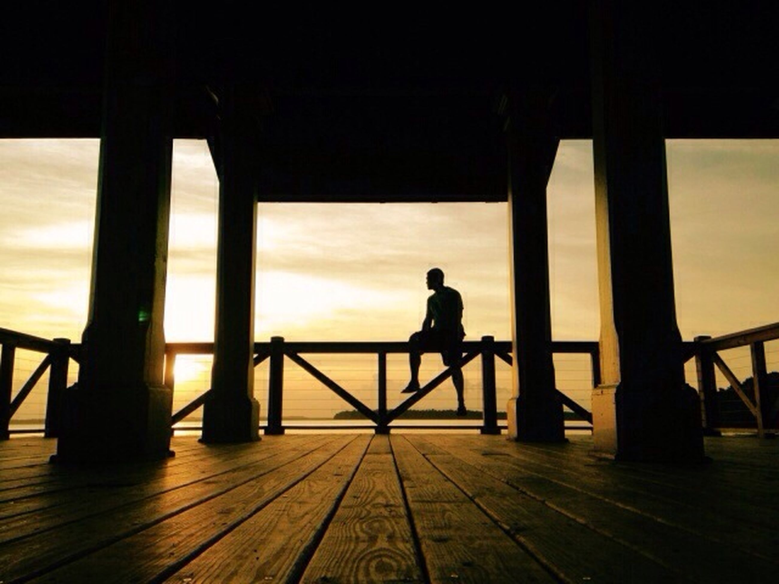 silhouette, men, sunset, lifestyles, indoors, leisure activity, transportation, full length, sky, person, railing, sitting, travel, mode of transport, standing, rear view, togetherness