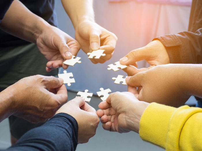 Closeup image of many people hands holding a jigsaw puzzle piece in circle together with sunlight effect. Business Teamwork Unity Communication Group Of People Hand Holding Human Body Part Human Hand Indoors  Jigsaw Piece Jigsaw Puzzle Leisure Activity Lifestyles Partnership People Puzzle  Real People Strategy Teamwork Together Together Concept Togetherness Togetherness Friendship Women