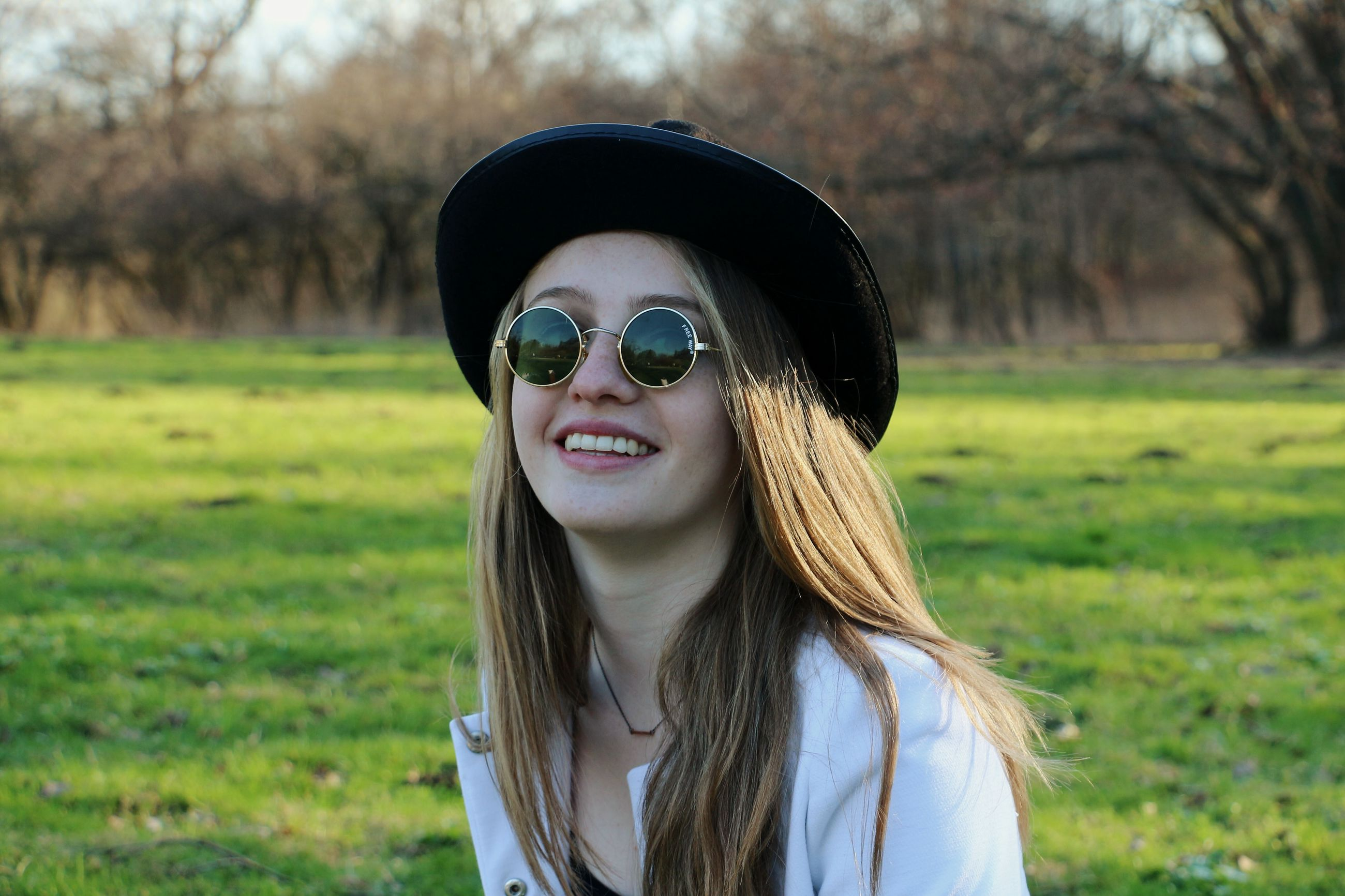 portrait, looking at camera, young adult, focus on foreground, person, front view, lifestyles, sunglasses, smiling, leisure activity, young women, casual clothing, headshot, grass, happiness, field, close-up