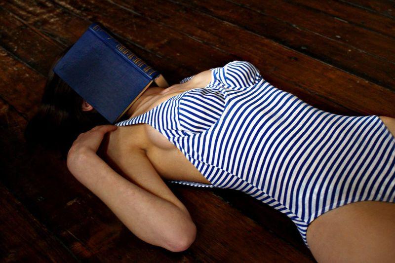 Woman in bodysuit with book lying down on hardwood floor
