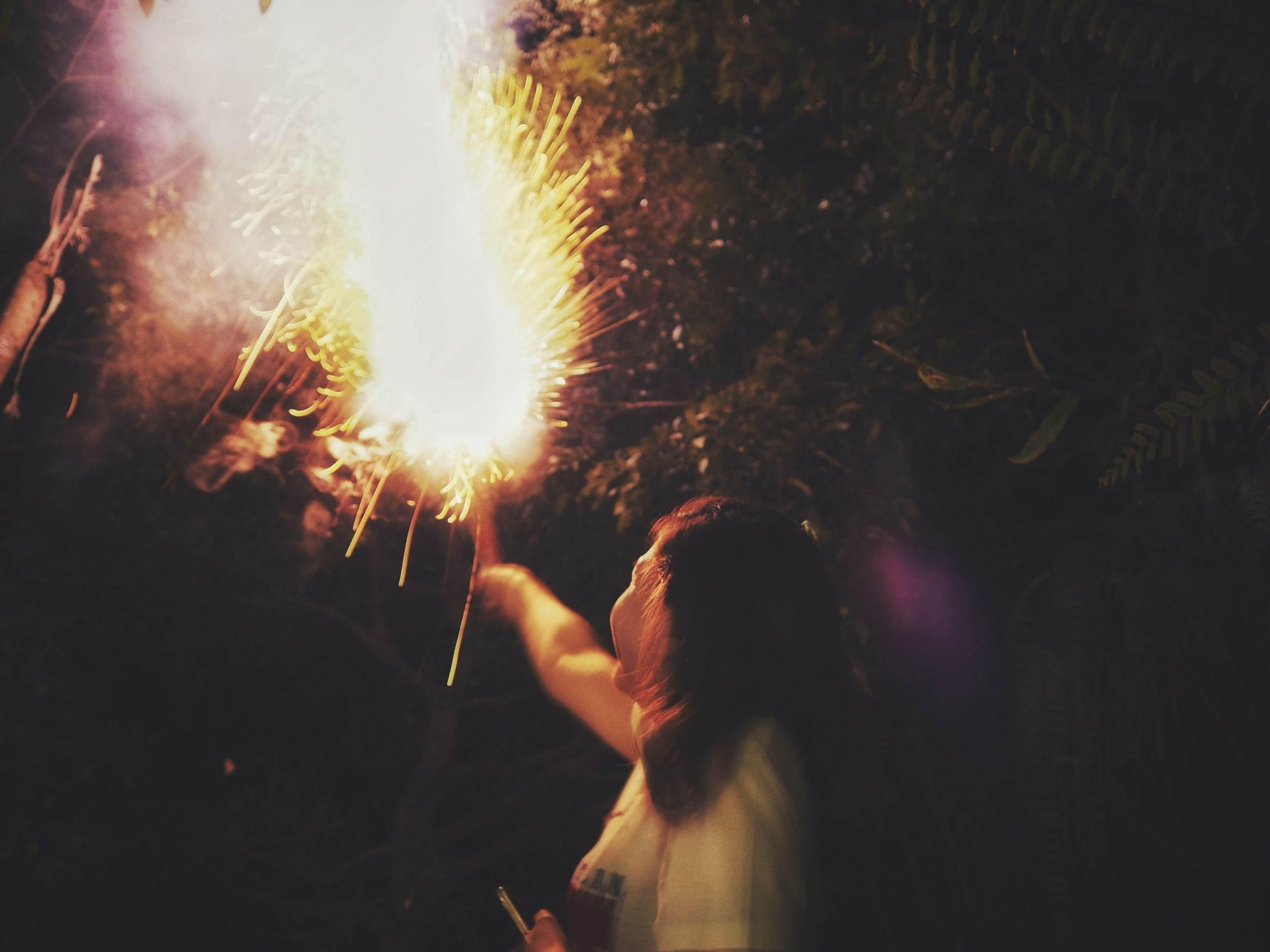 event, celebration, real people, motion, sparkler, glowing, blurred motion, illuminated, women, burning, firework, arts culture and entertainment, heat - temperature, firework - man made object, night, firework display, people, holding, leisure activity, long exposure, sparks, outdoors
