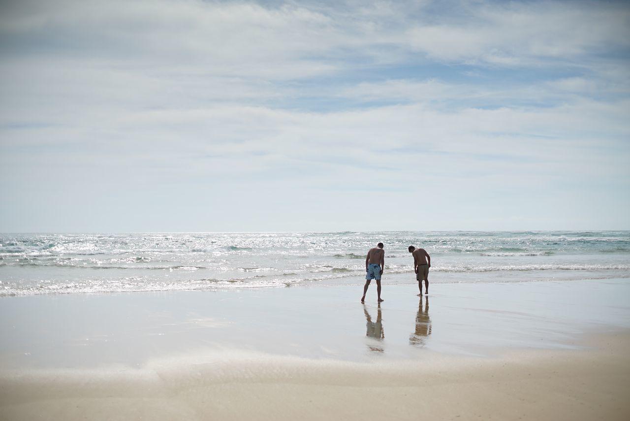 Men standing on wet shore at beach against sky