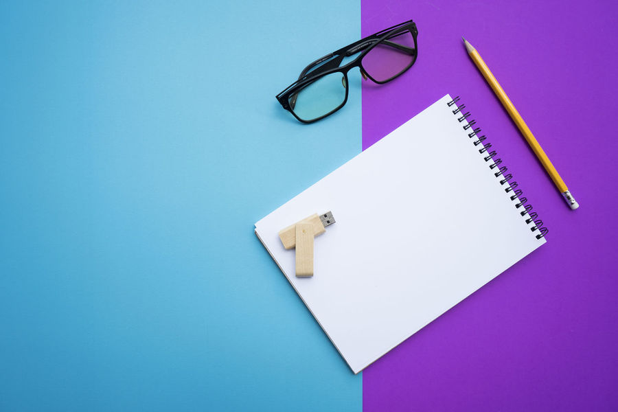 White notebooks, yellow pencil glasses and USB were placed on a purple-blue background. Business Flash Drive Office Student Write Blue Blue Background Book Close-up Colored Background Drawing Eyeglasses  Glasses High Angle View Message Note Note Pad Notebook Paper Pencil Purple Study Table Template Writing Instrument
