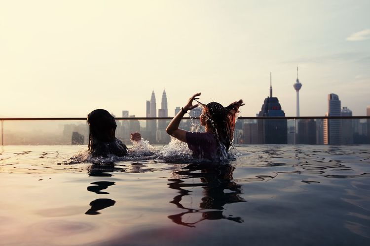 Women swimming in infinity pool during sunset