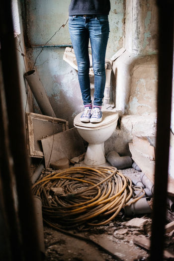 Low section of woman standing on toilet bowl at abandoned room