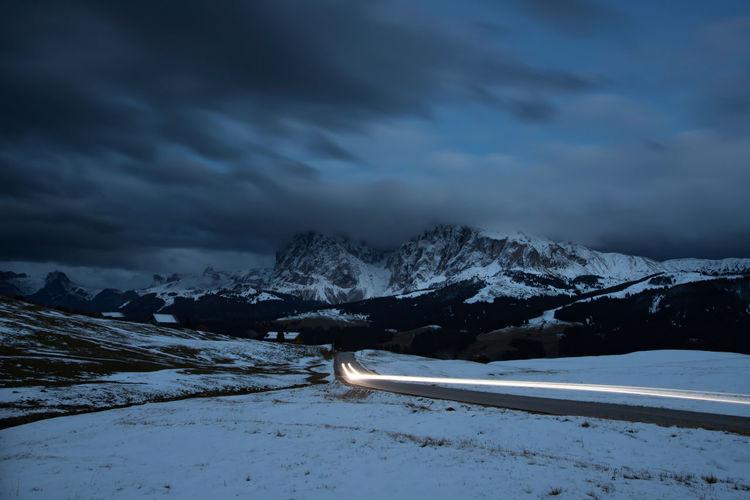 Light trails on road amidst snow covered landscape at dusk