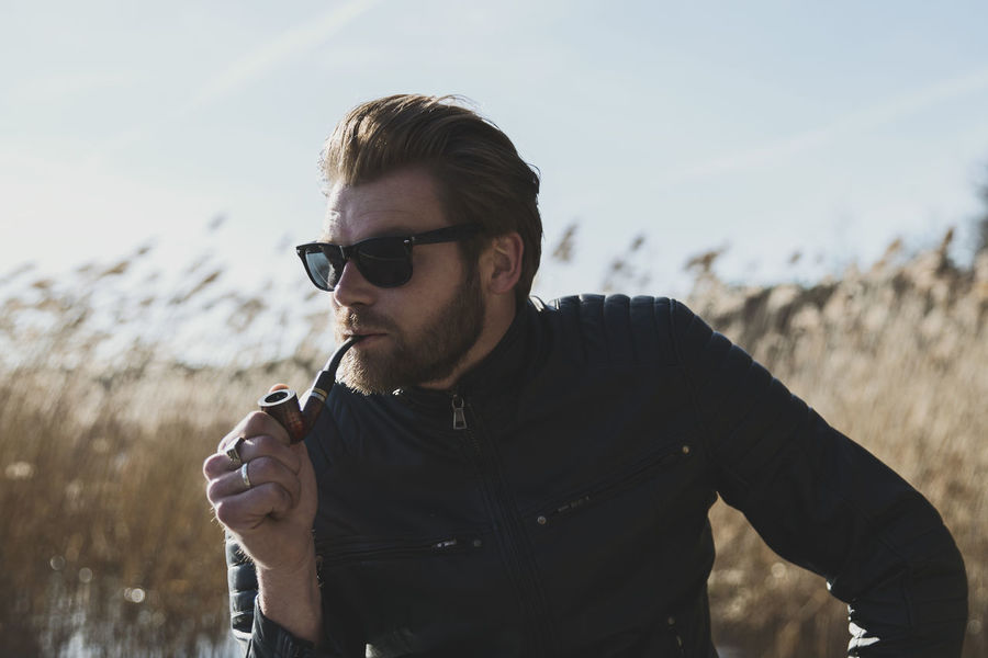 Adult men smoking Addiction Adult Adults Only Badass Beard Biker Casual Clothing Contrast Enjoyment EyeEm Gallery Focus On Foreground Front View Leather Jacket Lifestyle Lifestyles Looking One Person Outdoors People Pipe Real People Rocker Smoking Smoking - Activity Sunglasses EyeEm Selects EyeEmNewHere